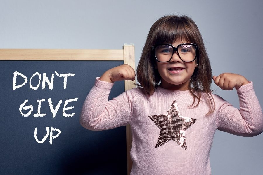 A happy girl with the word dont give up on the blackboard