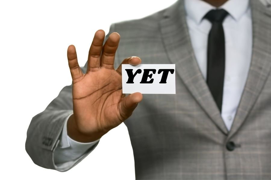 A man is holding a card with a YET word on it