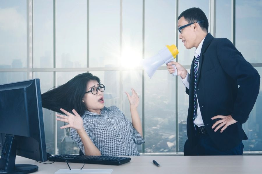 A shocked female employee being shouted by her boss